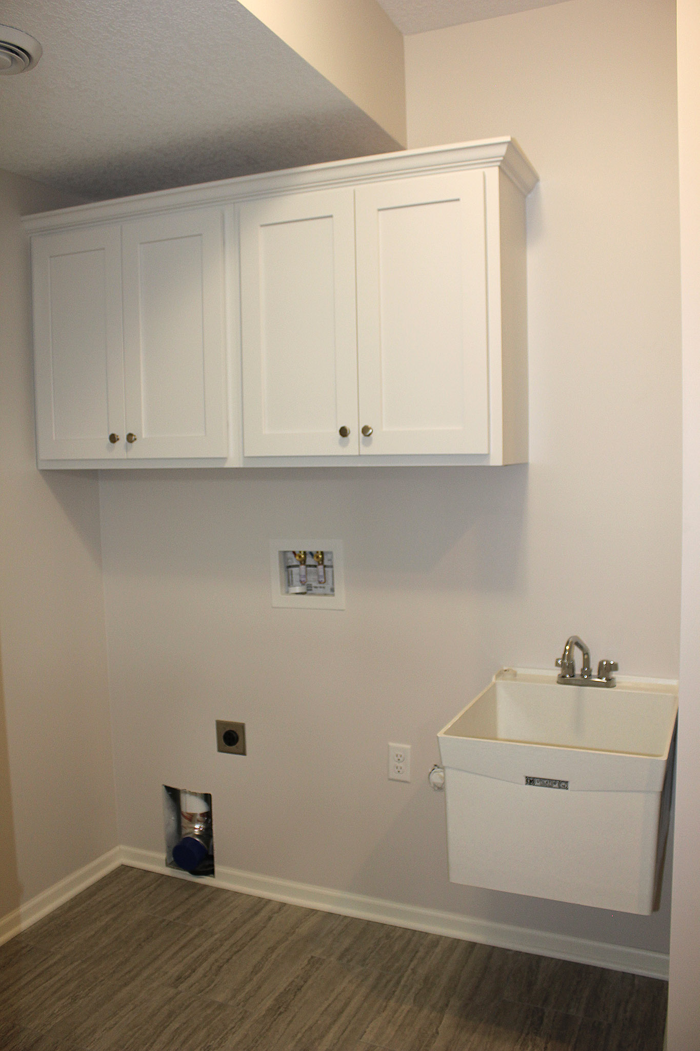 Laundry room with tub and cabinets