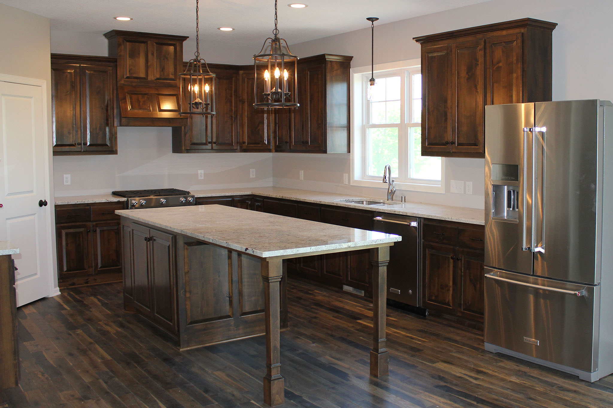 Kitchen island table with end seating area, stained poplar cabinetry and granite countertops