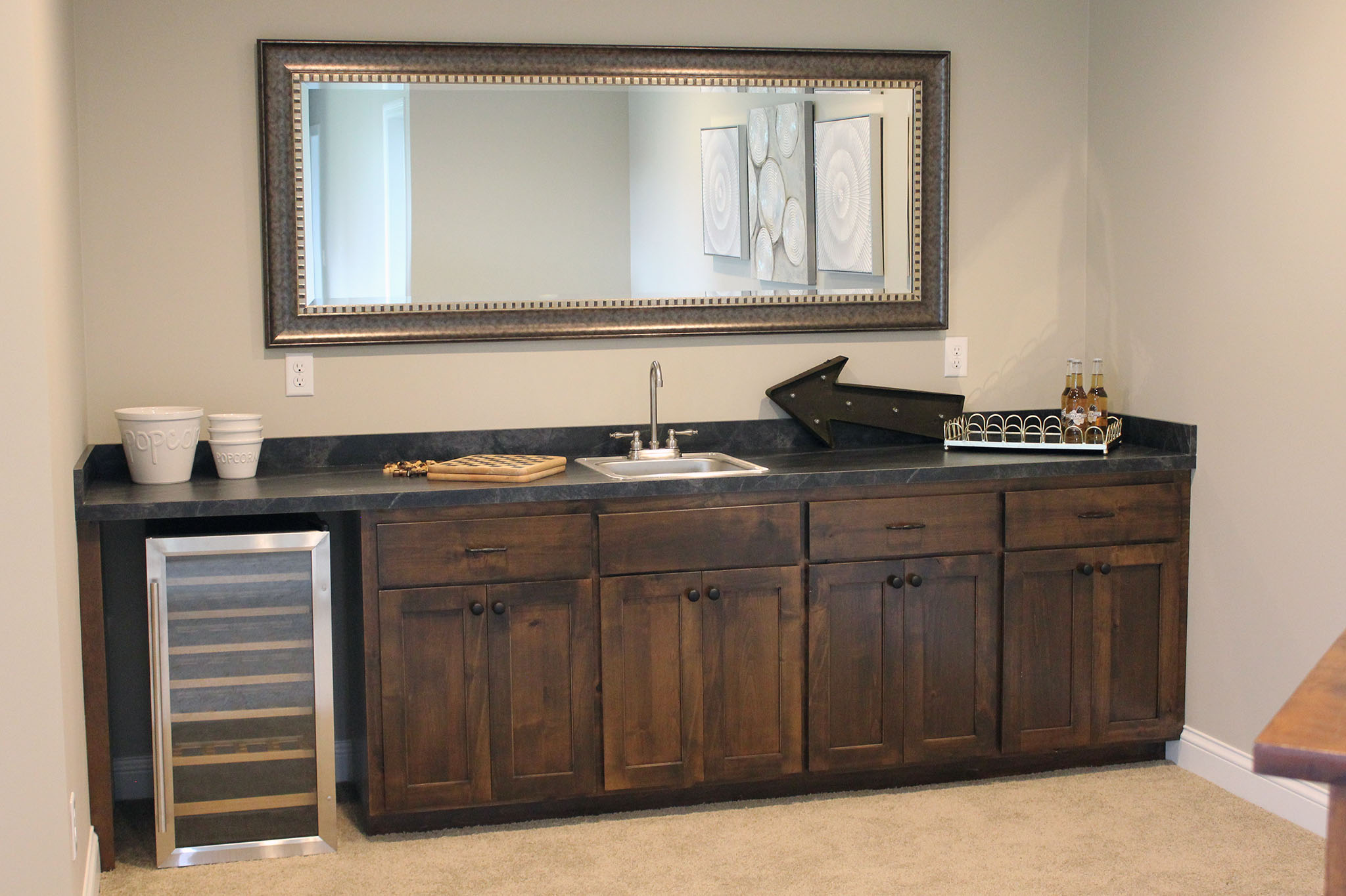 Basement single-wall wet bar with custom cabinets and granite countertops