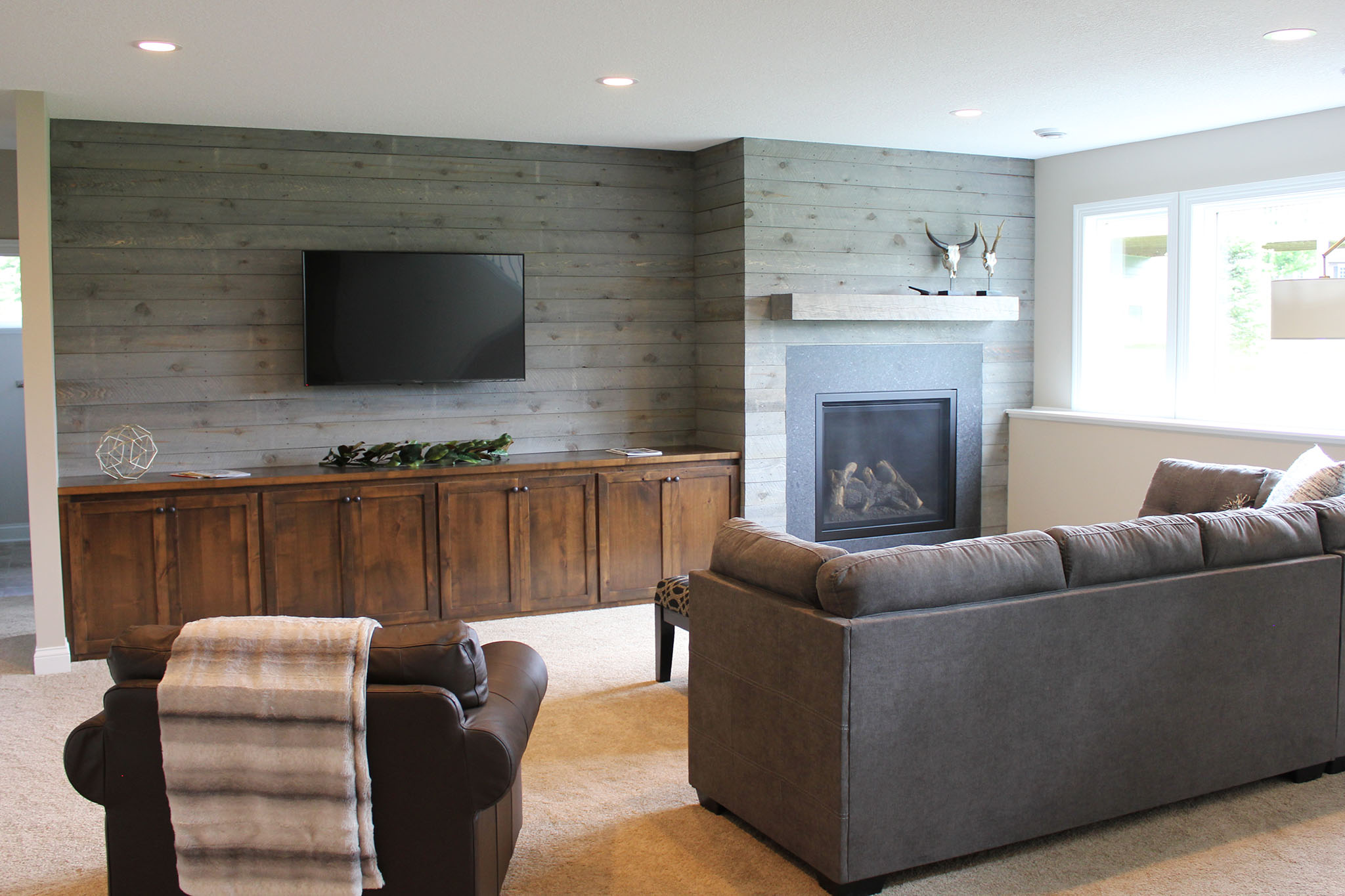 Lower level recreation room with shiplap wall, built-in cabinets and marble surround fireplace