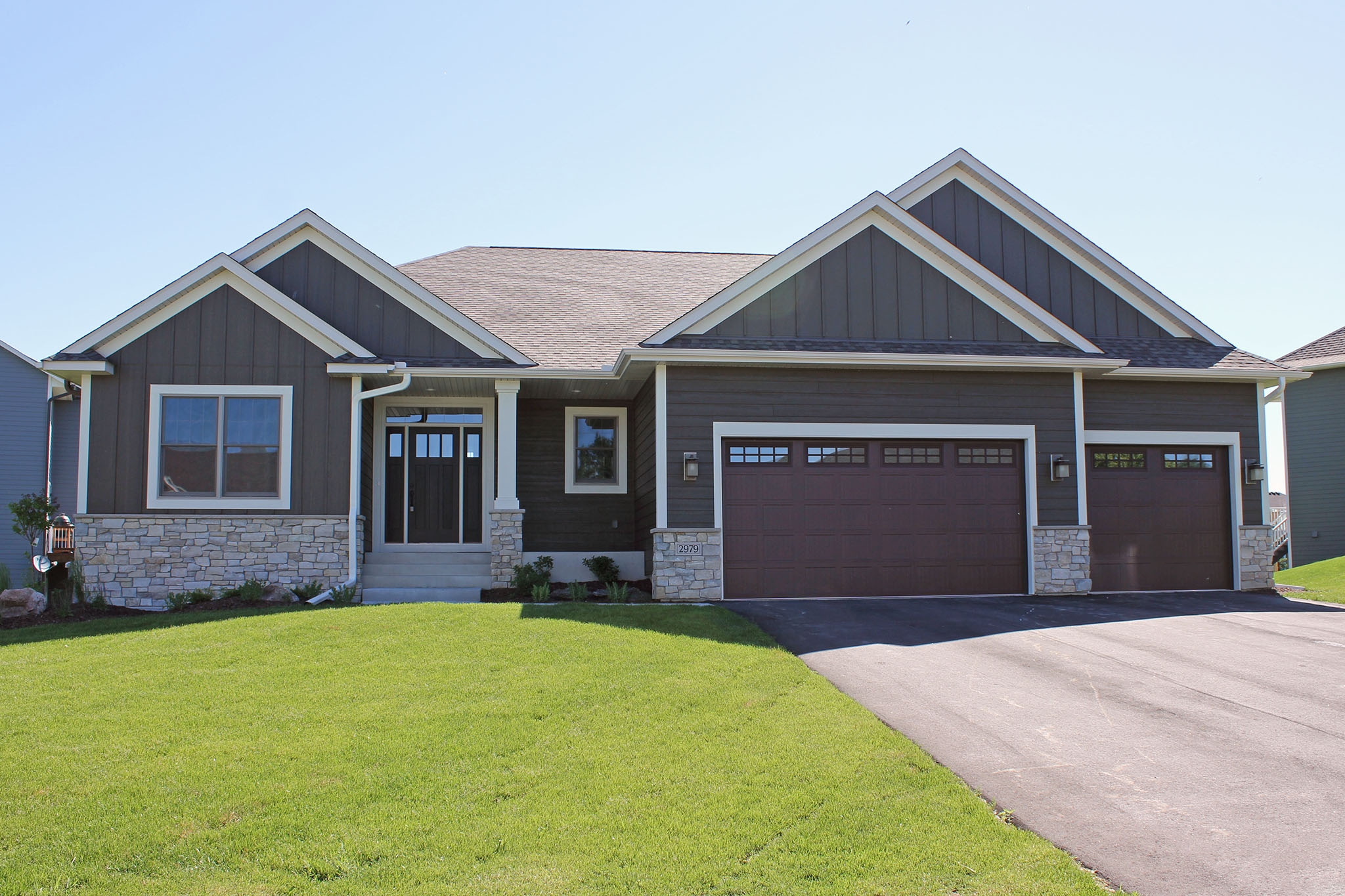 Three-stall garage rambler with stone wainscoat, board and batten siding and wide accent trim