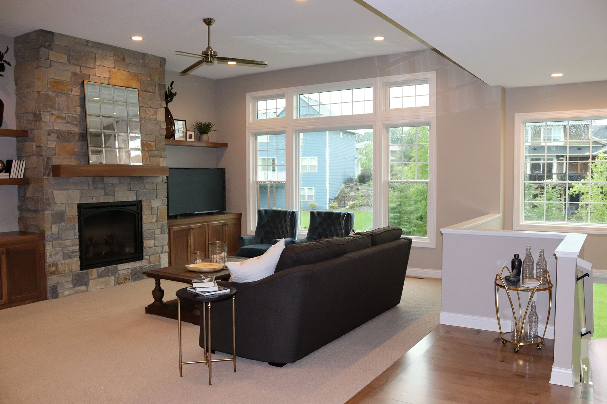 Open great room with massive stone gas fireplace, floating bookshelves and transom windows