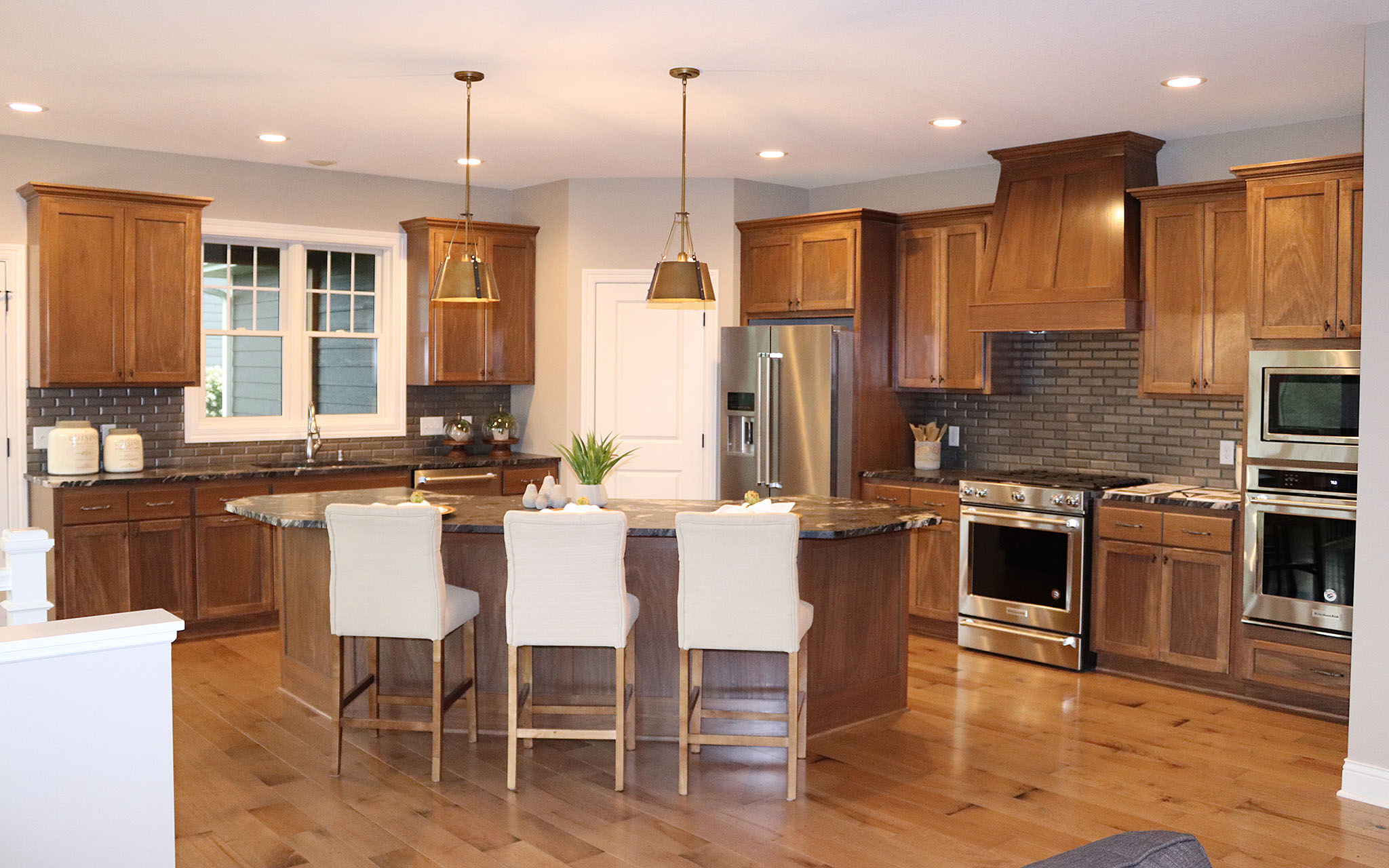 Eat-in gourmet kitchen with stainless steel wall oven, cooktop, walk-in pantry, granite countertops and stained poplar cabinets
