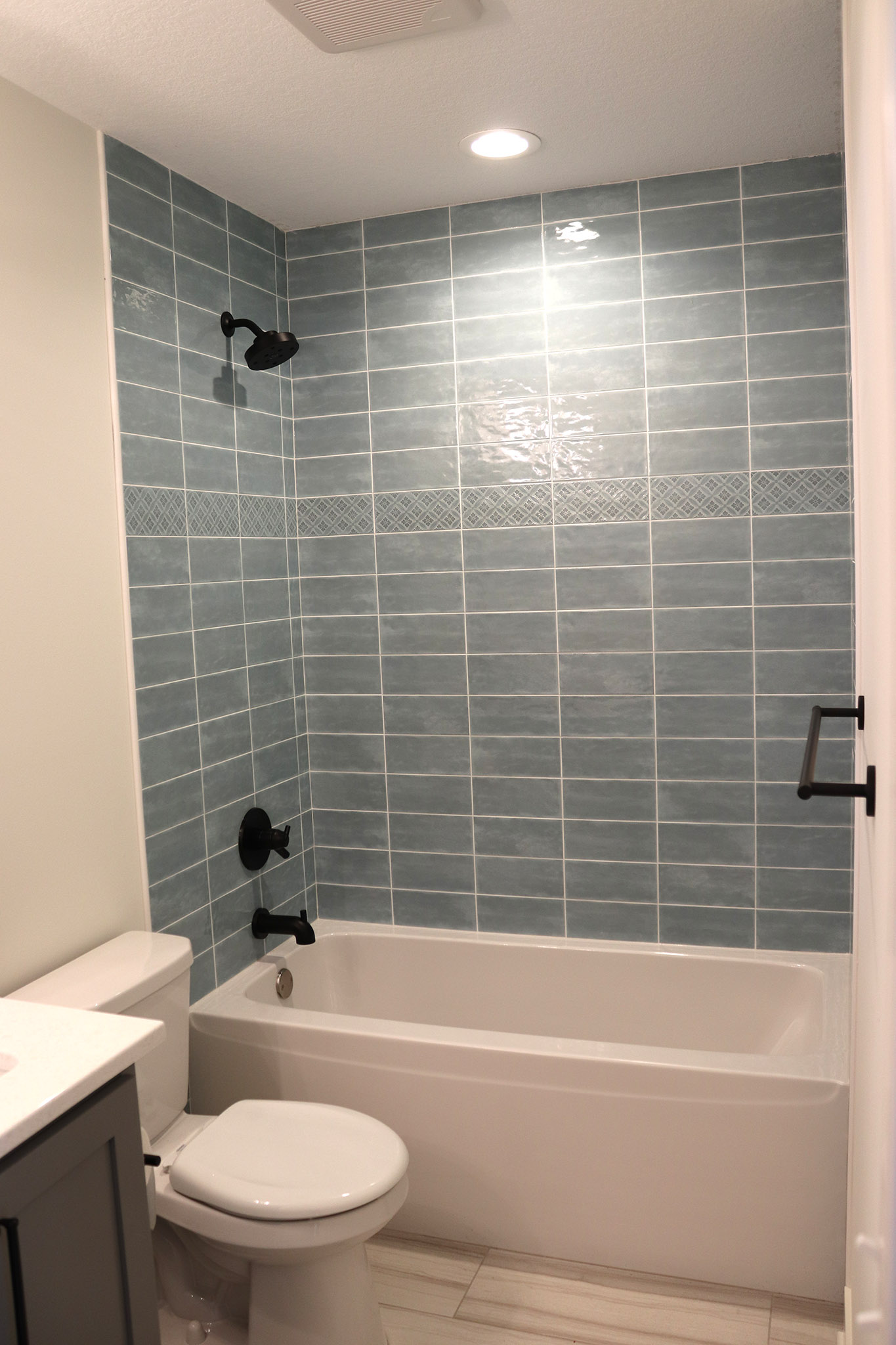 Kids bath with fiberglass tub, subway tile wall surround and accent border