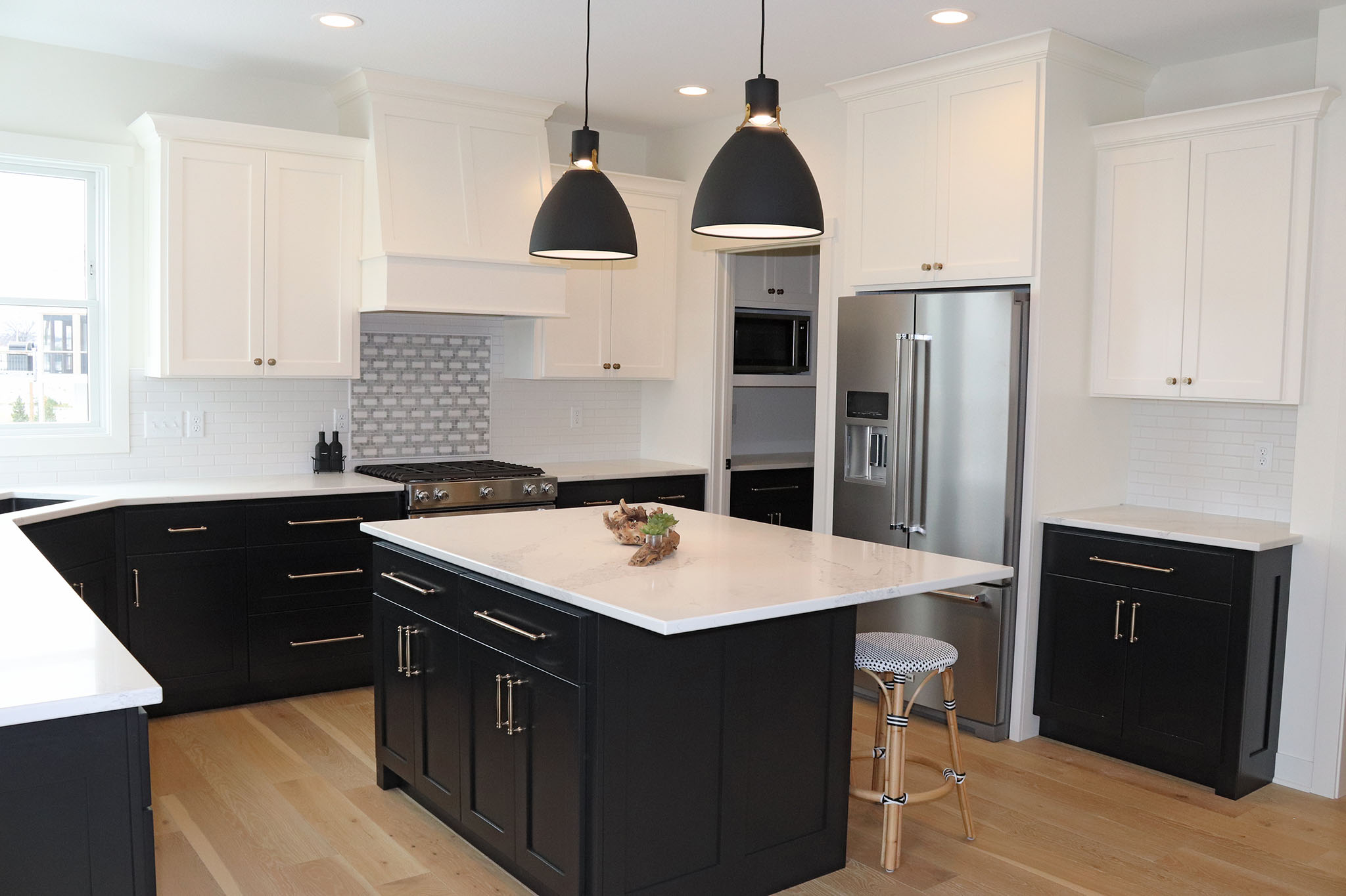 Sleek two-toned kitchen with black base cabinets, white subway tile backsplash and white upper cabinets