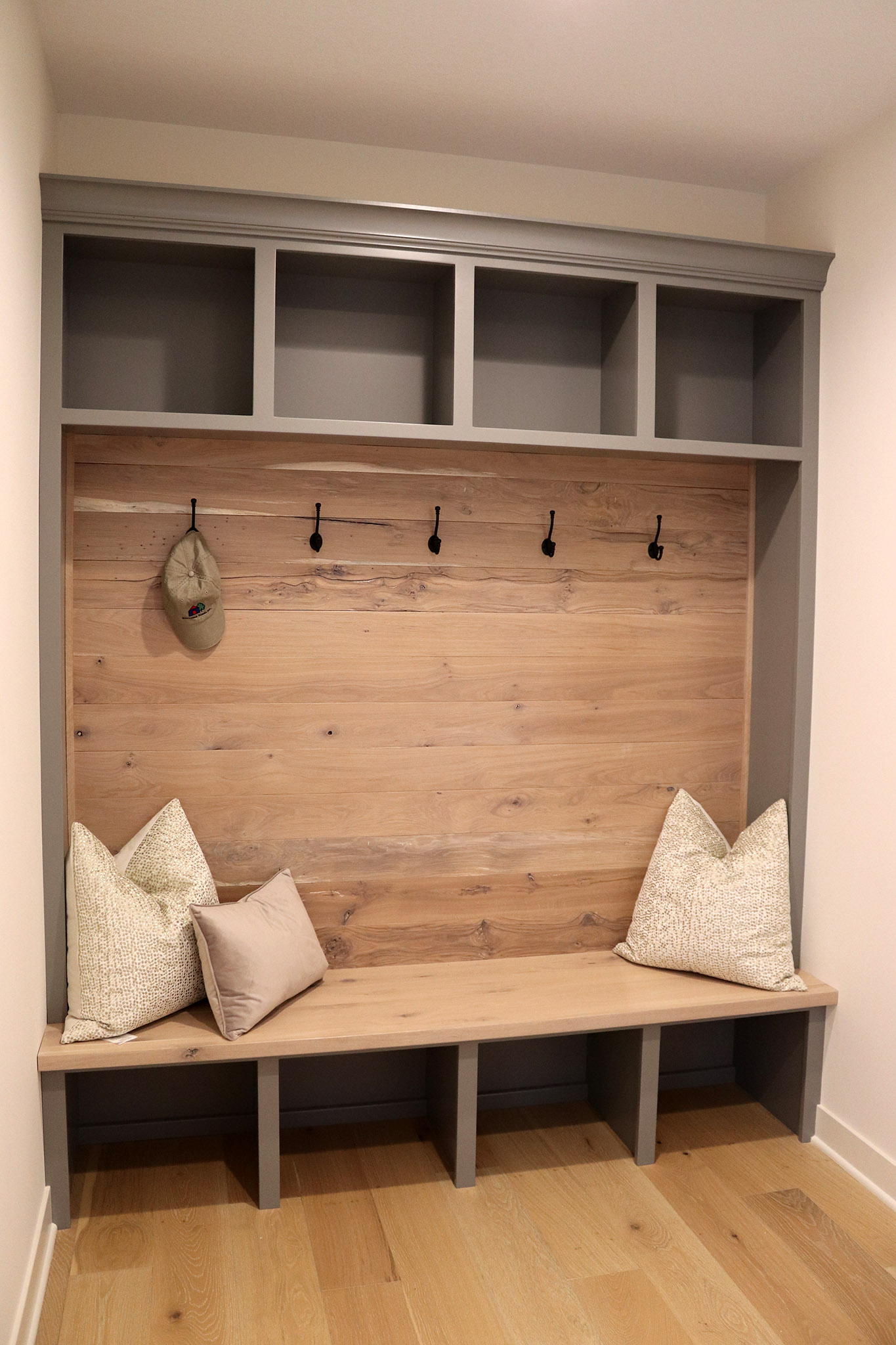 Mudroom lockers with coat hooks, open shoe storage below, open shelves above with shiplap wood accent and bench