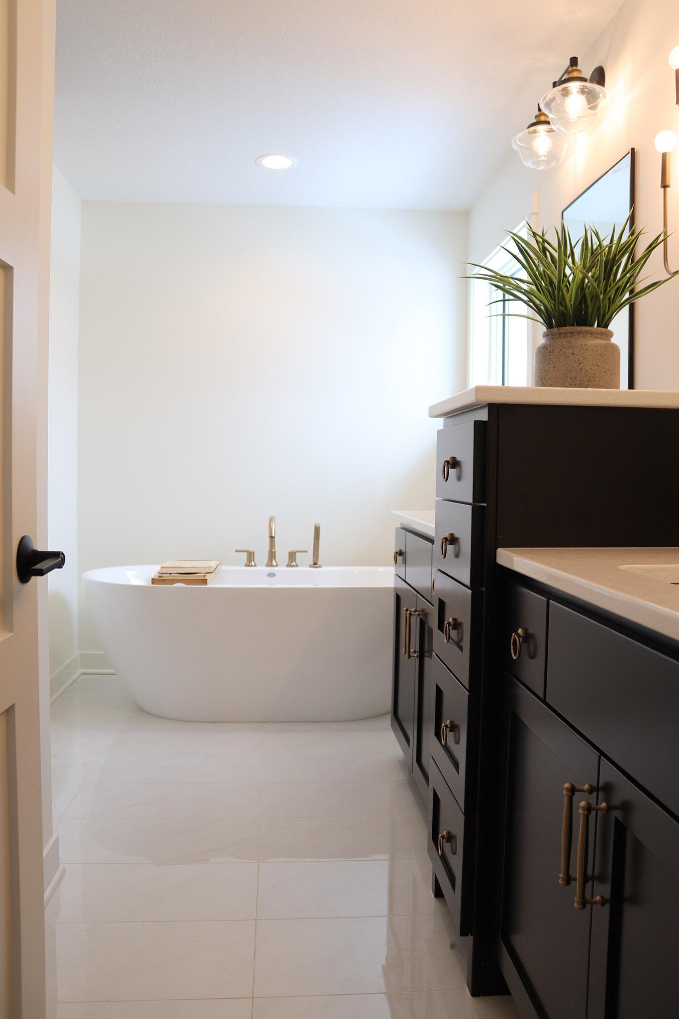 Master bath with free standing tub, custom cabinet vanity and granite vanity tops