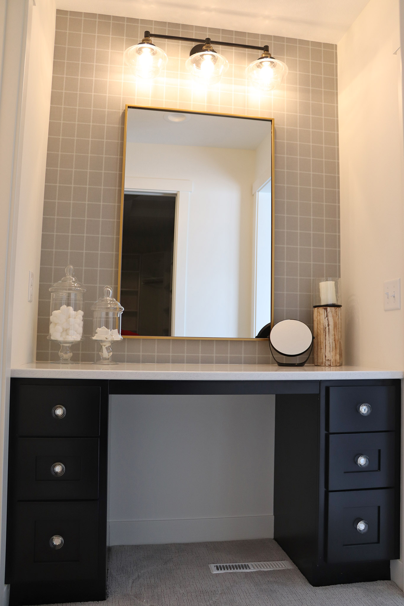 Modern built-in makeup vanity with custom cabinets, granite top and wallpaper background