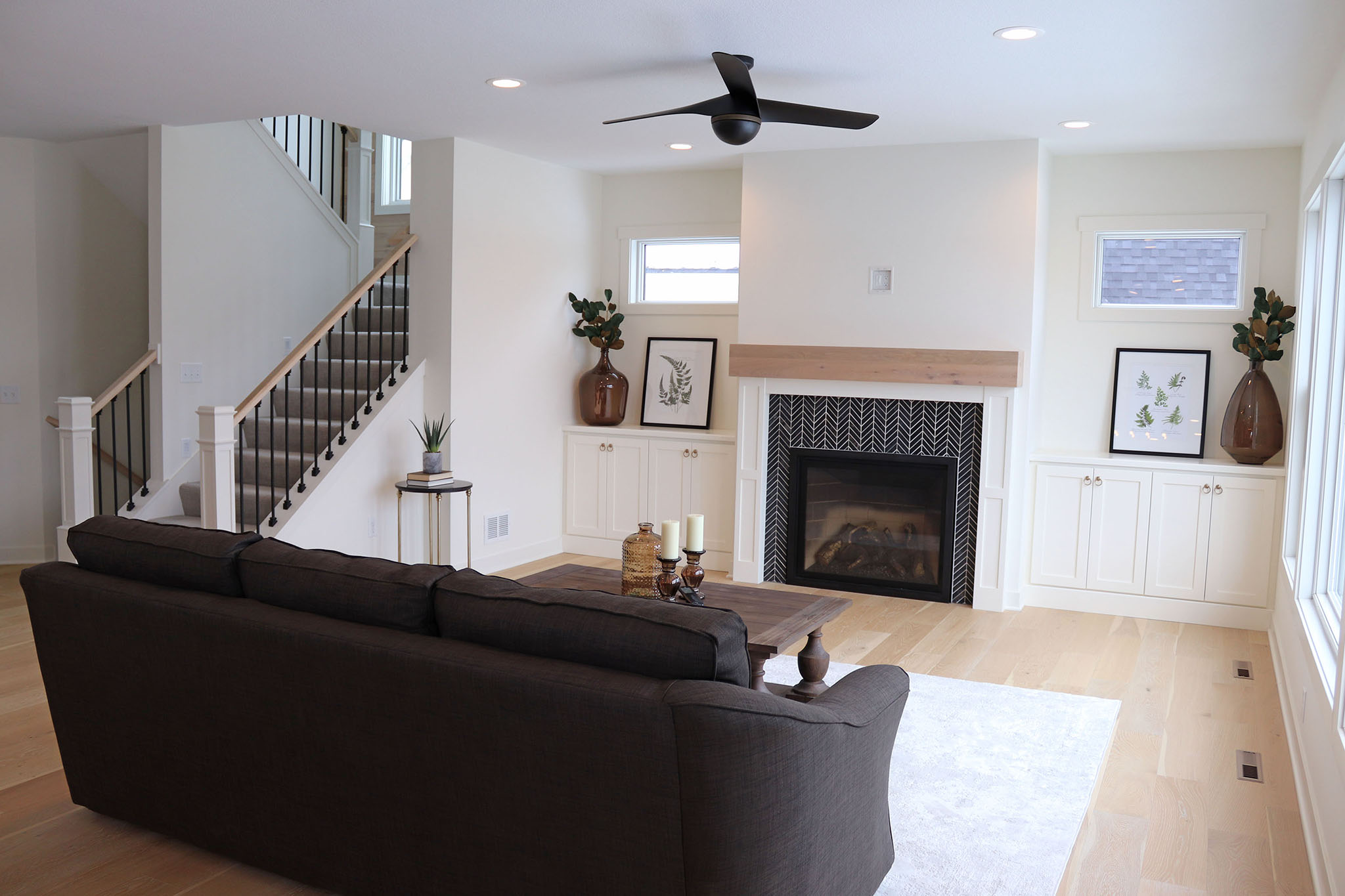 Contemporary great room with tile surround fireplace, custom cabinets, transom windows and metal baluster railing