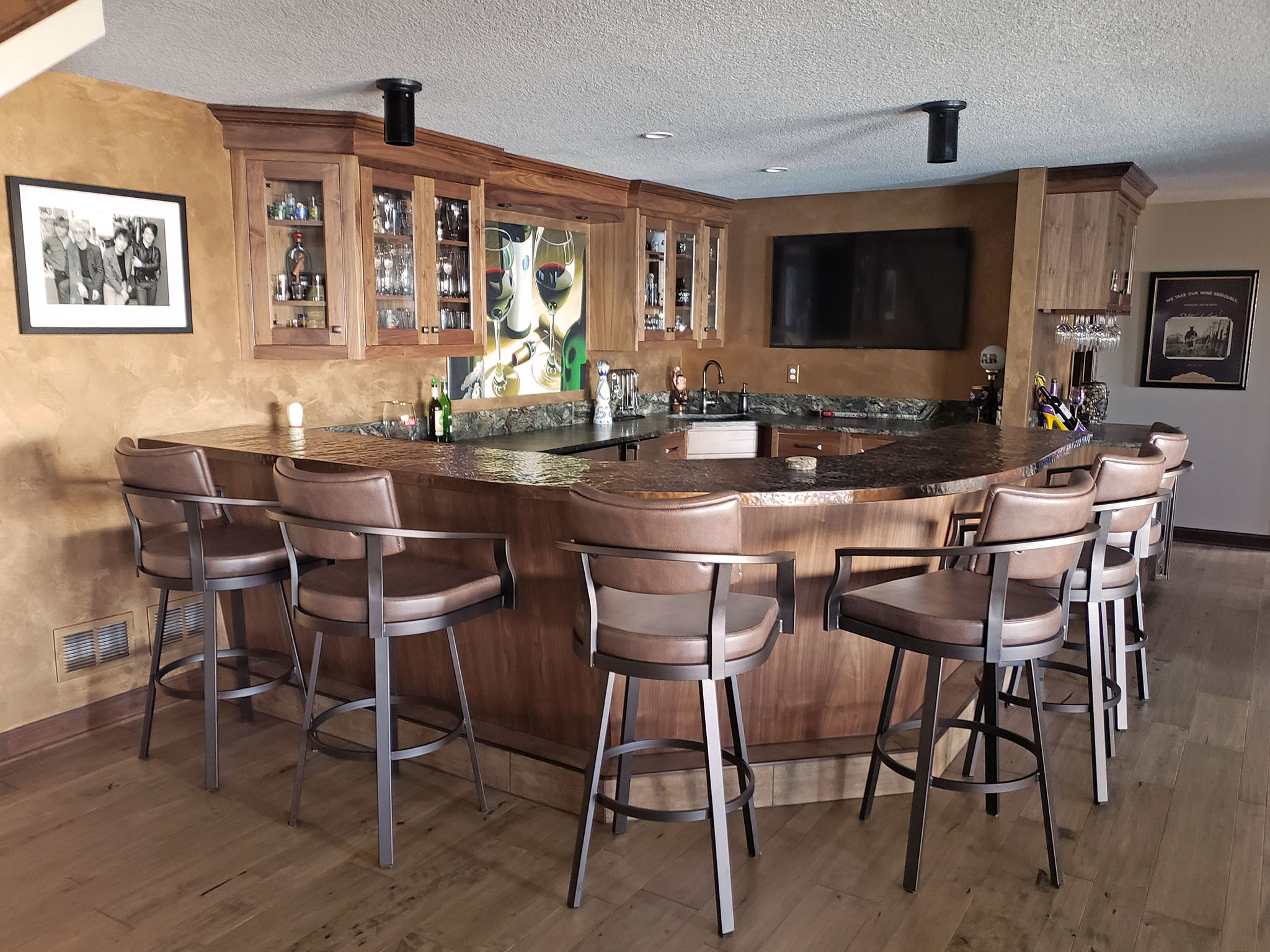 Cozy basement bar featuring custom wood cabinetry and copper countertops