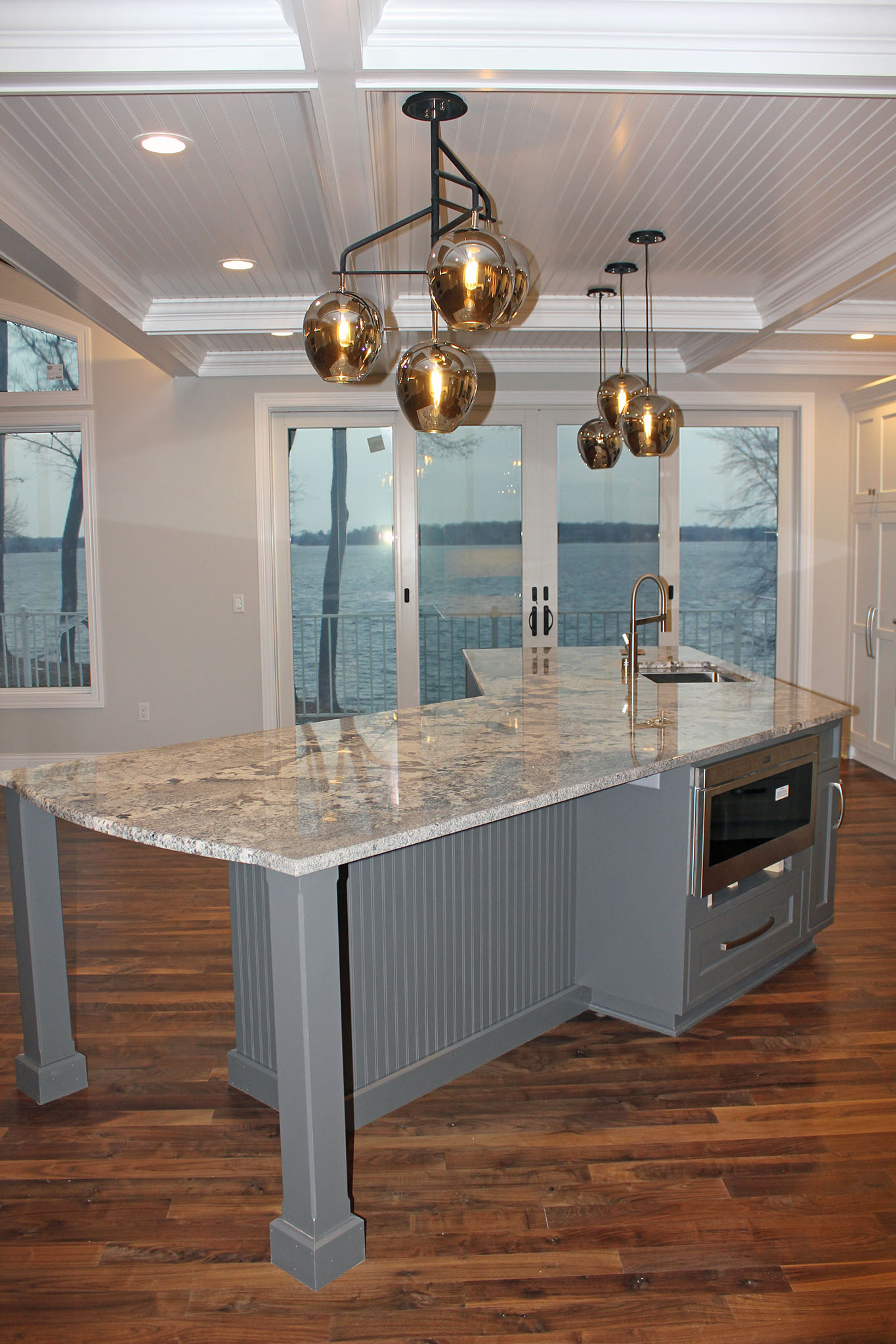 Closeup of kitchen table-style island, painted beam ceiling and hanging pendant lights