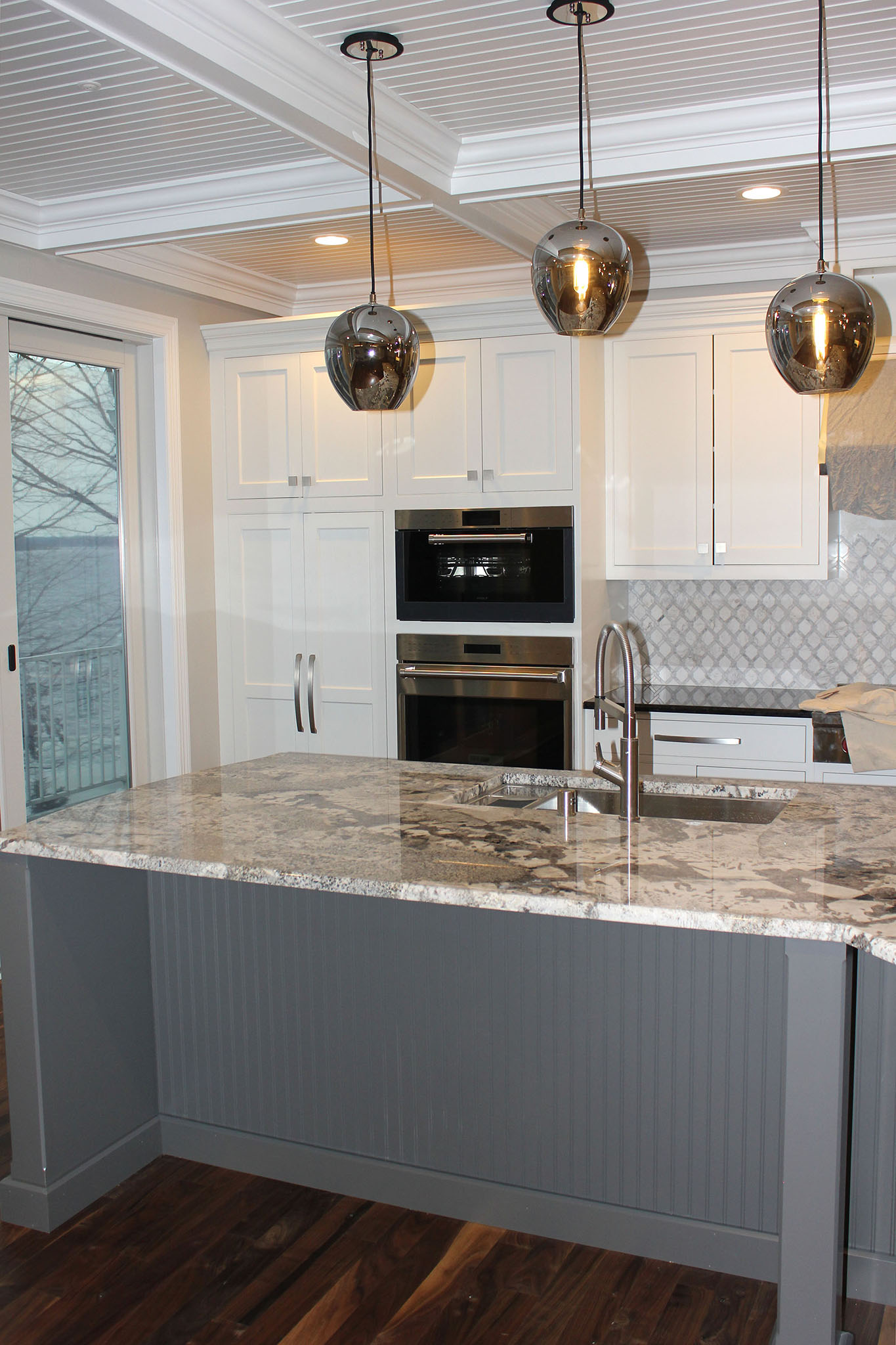 Closeup of kitchen custom island with granite countertops, double ovens and white beam ceiling