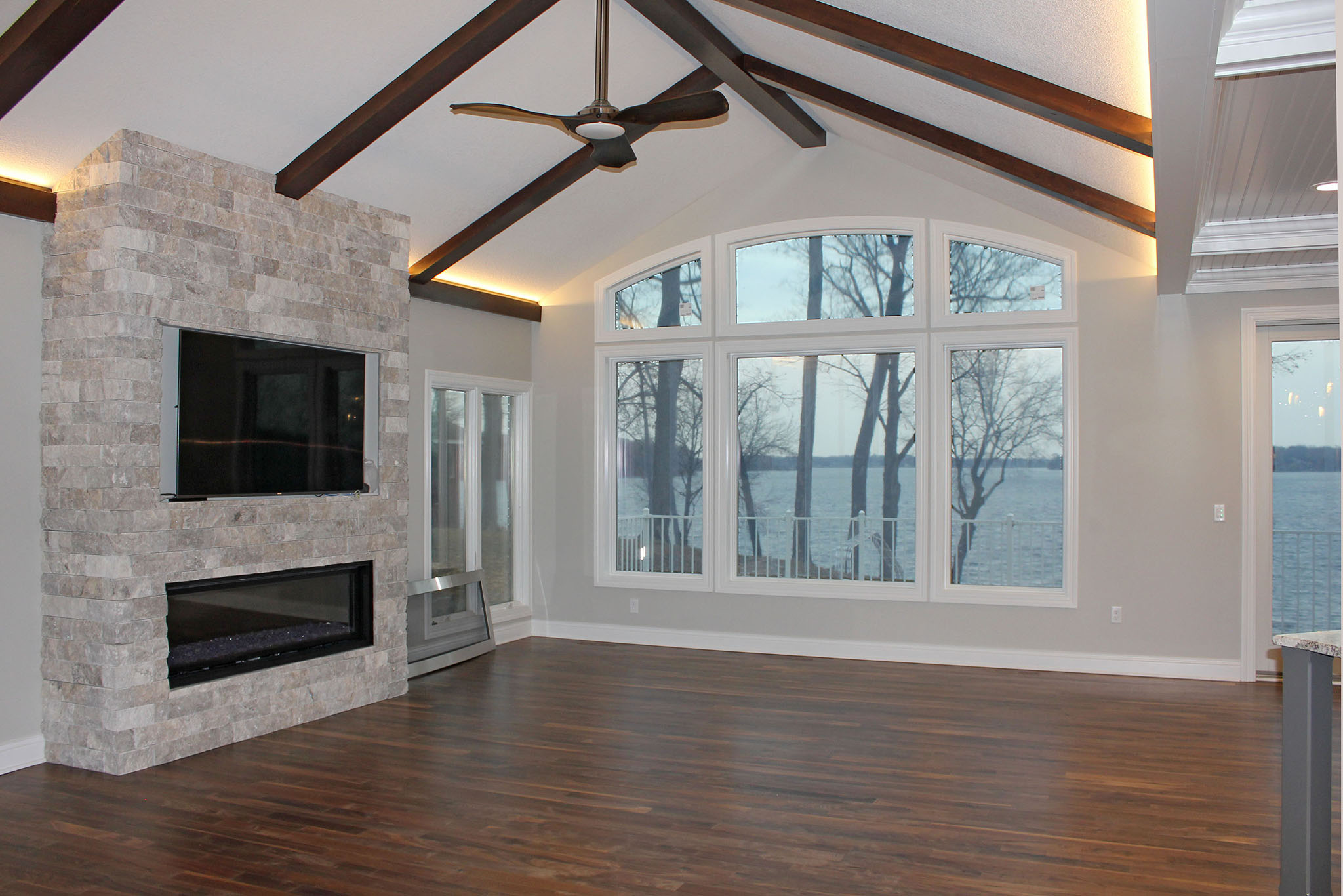 Great room with stone fireplace, wood beam ceiling and arched windows overlooking Lake Minnetonka