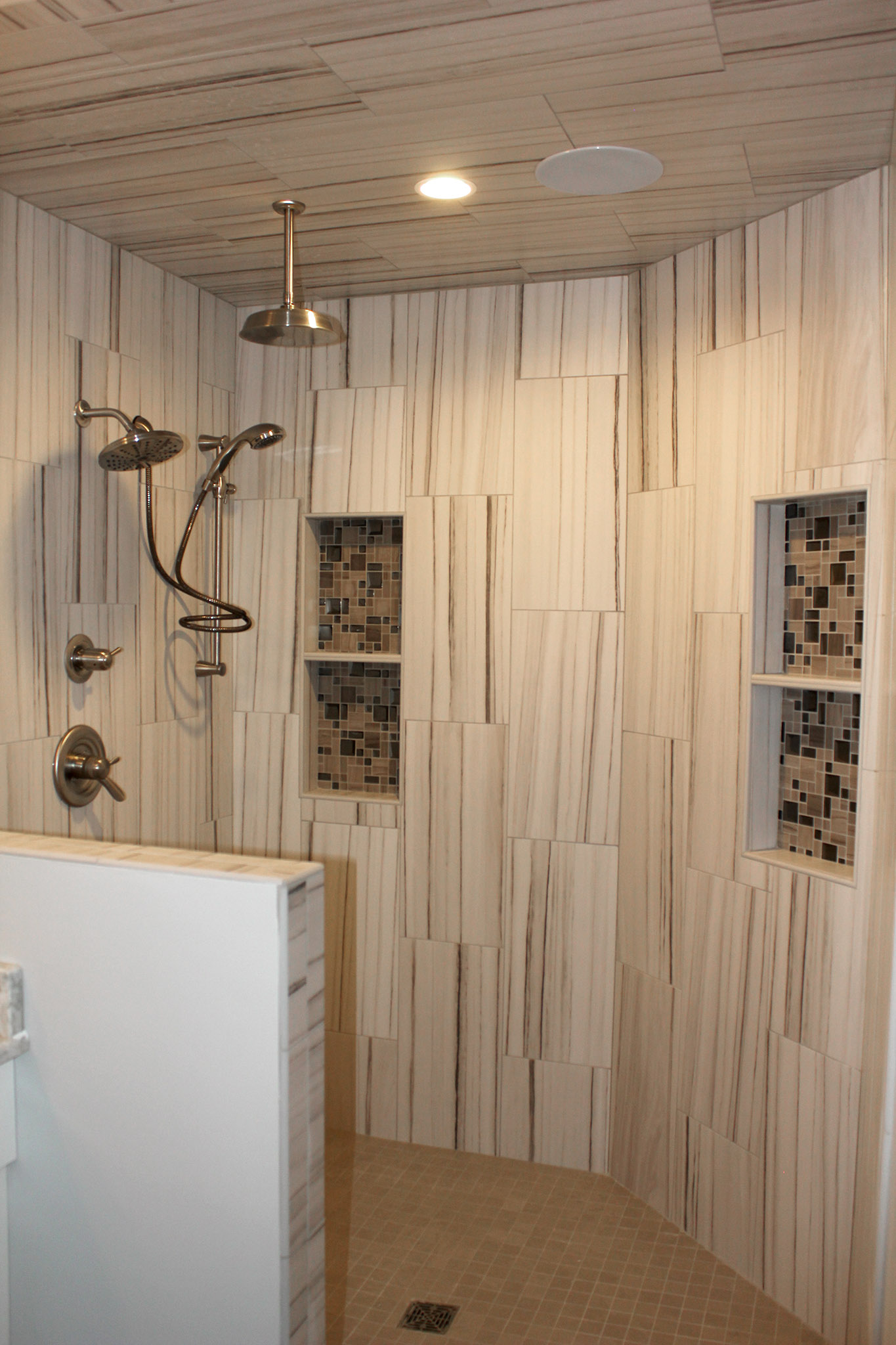 Spacious luxury door-less walk in ceramic tile shower with inset shelves and rain shower head