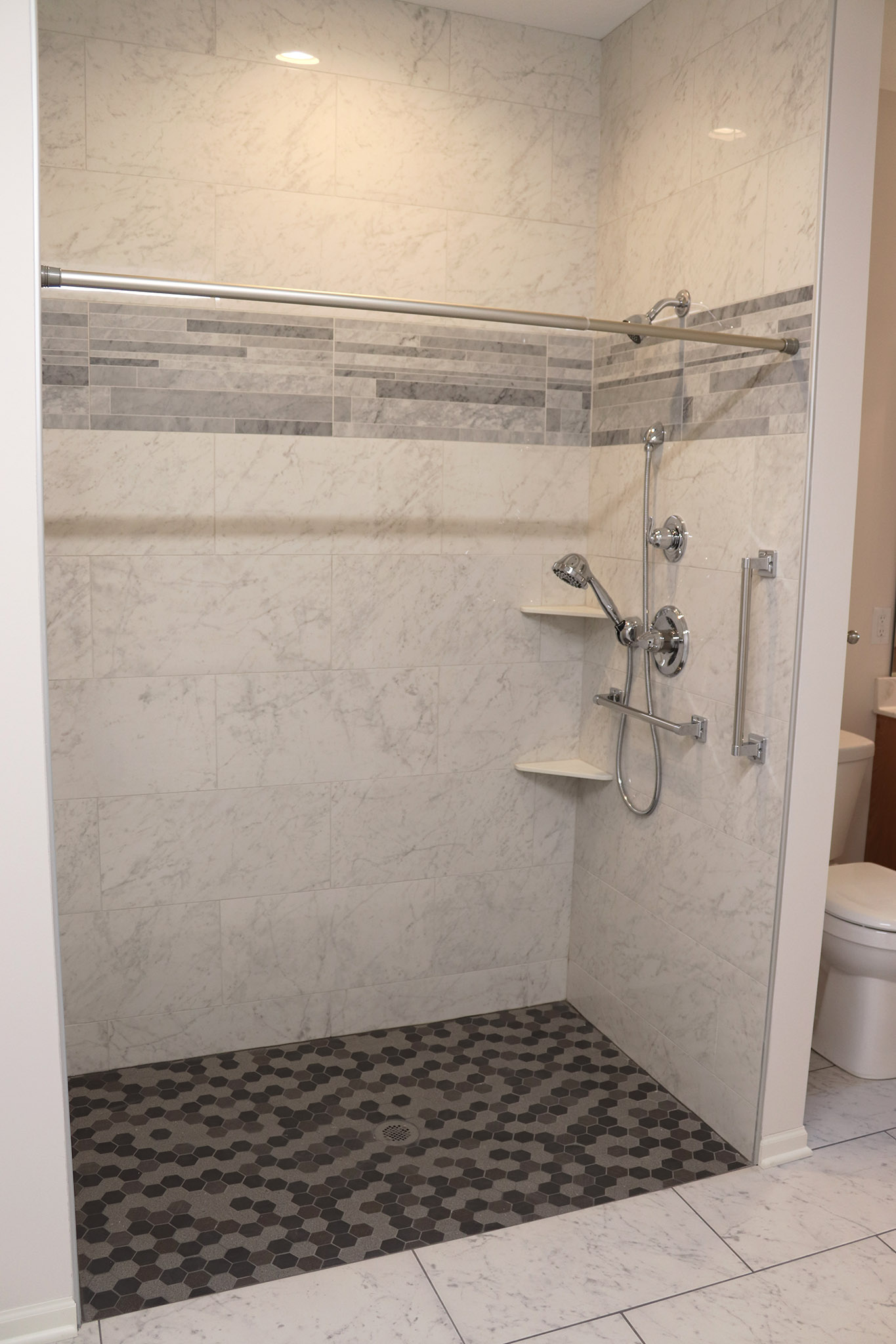 Shower with tile accents and corner shelves