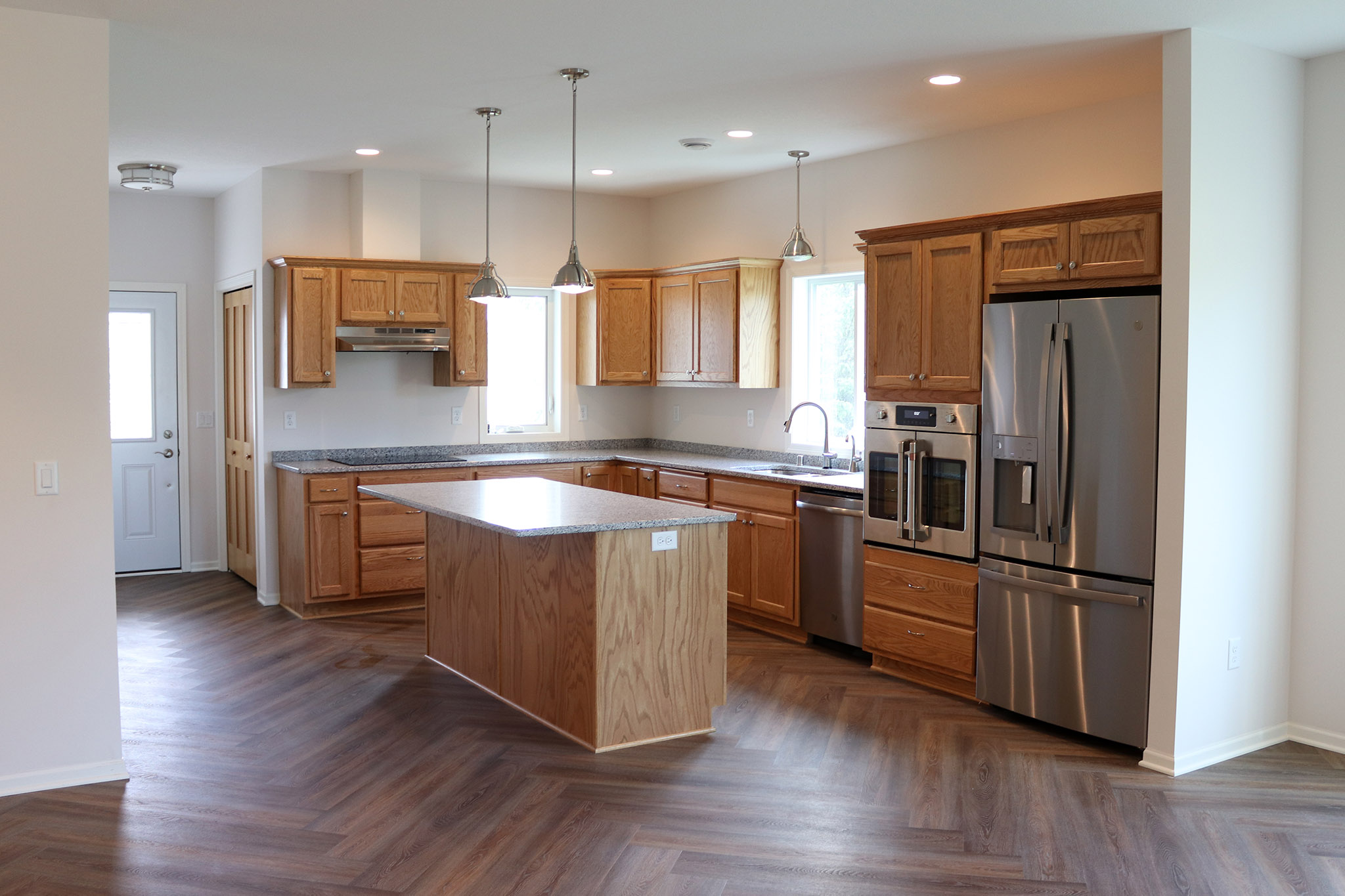 Kitchen with wood cabinets, stainless appliances and herringbone wood floor