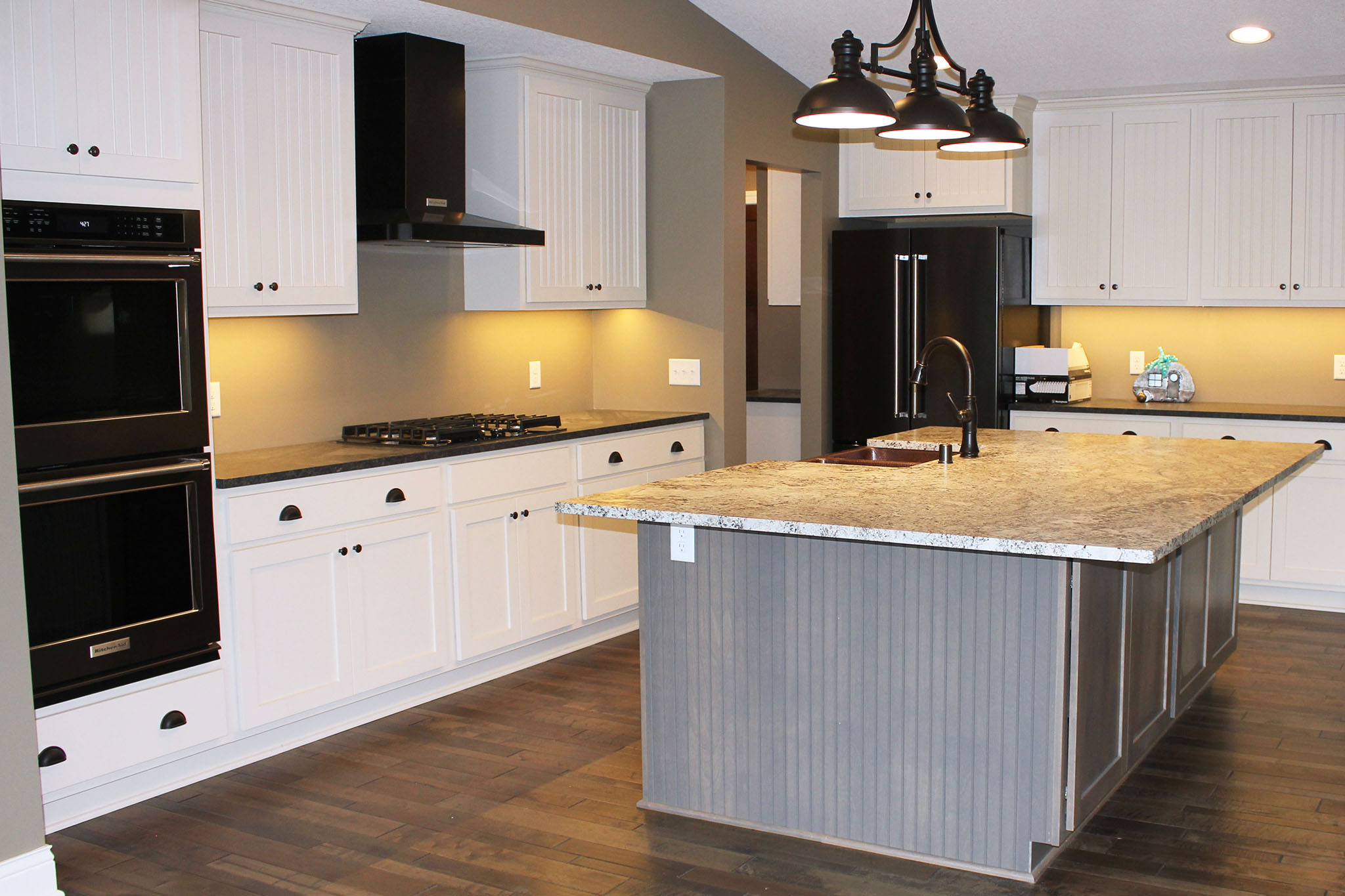 Modern white kitchen with wood island and granite countertops