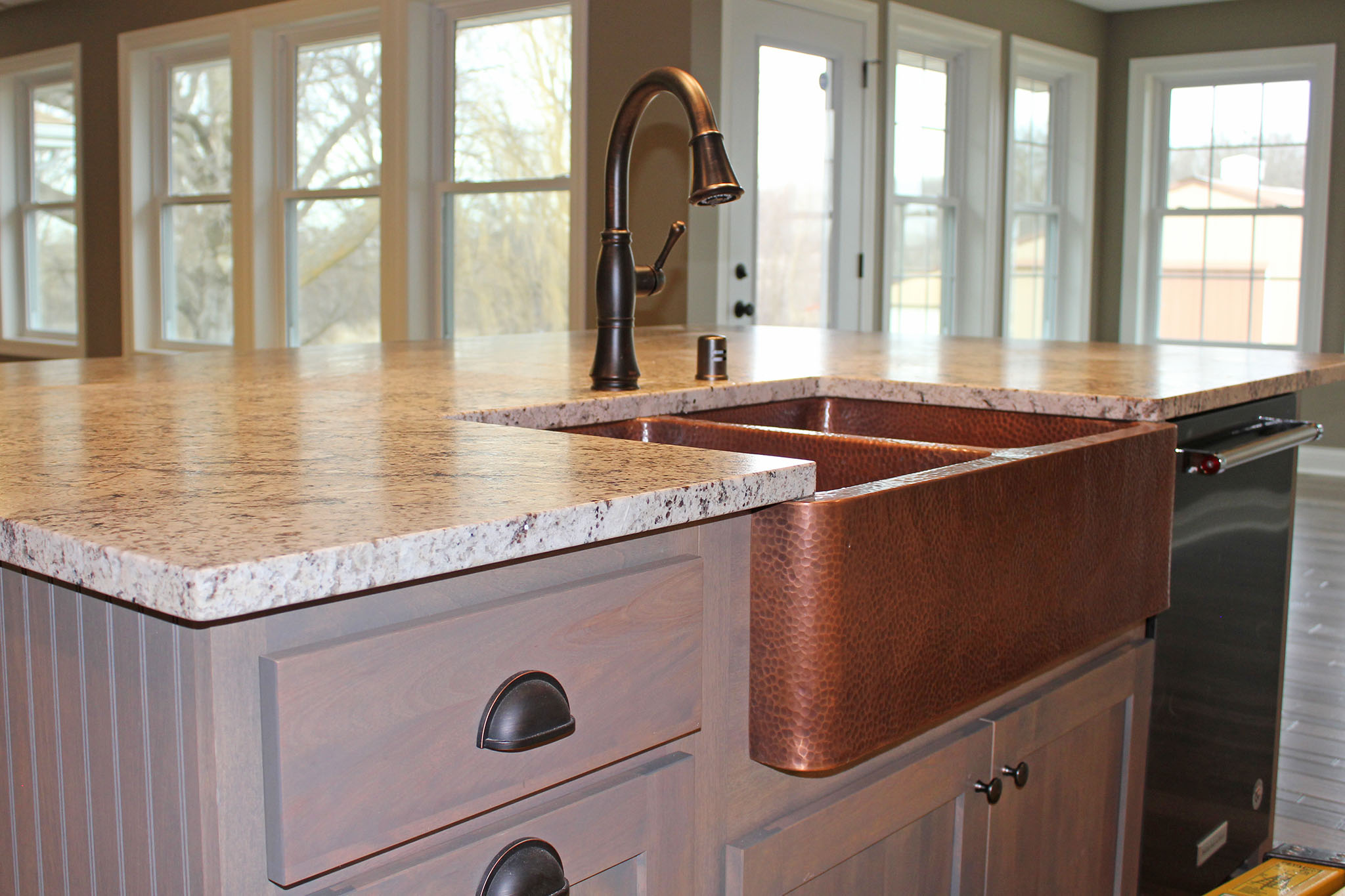 Closeup of kitchen island with copper sink and granite countertops