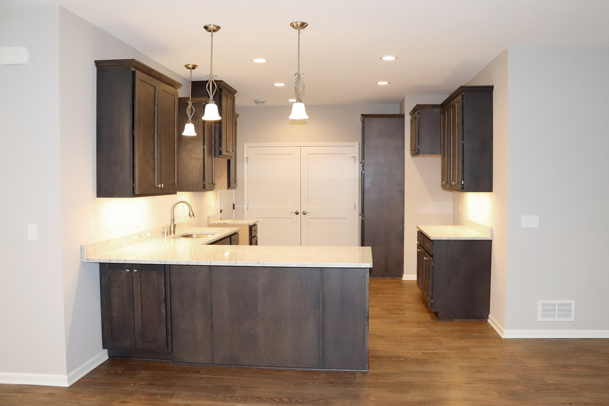 Kitchen with dark wood cabinets and light countertops